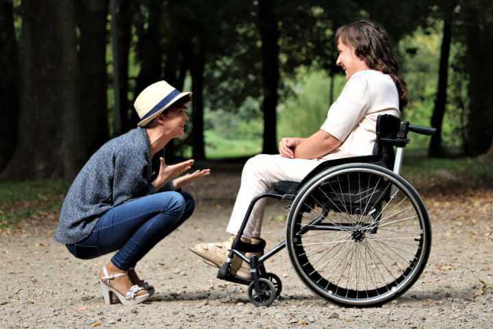 Devojka čuči pored majke koja je u kolicima za nepokretne