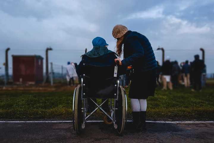 Pacijent u kolicima za nepokretne sa devojkom u prirodi