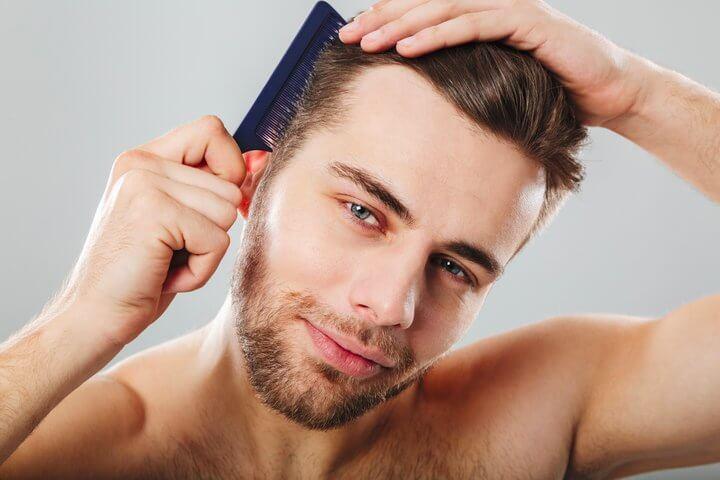 Muškarac koji češlja svoju braon kosu