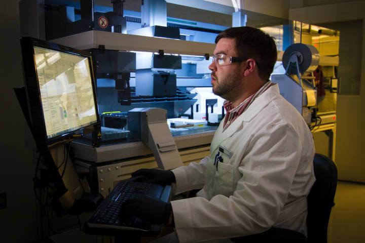 Naucnik u belom mantilu sedi ispred računara na kom vrši istraživanje
